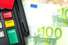 Close up of botton on credit card machine with the red credit ca. Rd on top with euro banknote background and copy space. Concept of choice enter into be debt or Stock Photo