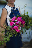 Close up bouquet. Adult woman florist demonstrates flower bouquet on background of the sea or Ocean and stones summern royalty free stock image