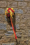 Close-up of a bouquet of colorful flowers hanging from a stone wall in a lane of Orvieto. stock photography
