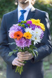 Close-up of  bouquet in teenager boy hands. Close-up of  bouquet of different colorful flowers in teenager boy hands Royalty Free Stock Photos