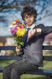 Close up of bouquet in teenager`s hand, teenager looks at his watch. Close up of spring colorful bouquet in teenager`s hand, teenager looks at his watch, first Royalty Free Stock Photo
