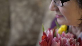Close up bouquet of tulips in old woman's hand. Young girl with a tender flower stock video footage