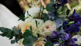 Close-up Of A Bouquet And Various Delicate Flowers. Lies On The Background Of A Blurry, Elegant Bride And Groom On A Sunny Warm Summer Day In Nature. Concept Of stock video footage