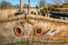 Closeup of a ship`s bow. Close-up of the bow of a weathered and rusted old iron ship moored in a Dutch river Royalty Free Stock Image