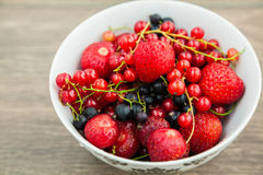 Close-up bowl with berries. Bowl with strawberries, blackberry and red currant royalty free stock photos