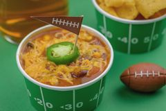 close up of bowl of chili with jalepeno pepper and football flag royalty free stock photos