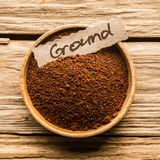 Close up of a bowl of ground coffee. Close up of a bowl full of ground coffee over an old wooden table Royalty Free Stock Image