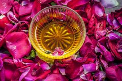 Close up of a bowl of honey,Fructose on rose,rosa petals. royalty free stock image