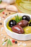 Close-up of a bowl with olives in olive oil and spices on a wood Stock Photography