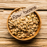 Close up of a bowl of raw coffee beans. Over an old wooden table Stock Photo