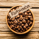 Close up of a bowl of Robusta coffee beans. Over an old wooden table Stock Image
