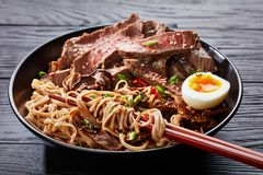 Close-up of a bowl of Soba noodles and beef. Close-up of a bowl of Soba noodles with sliced roast beef steak, shiitake mushrooms, half of hard boiled egg and stock photo