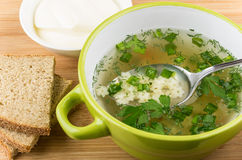Close up of bowl with soup, bread, mayonnaise and spoon Stock Photo