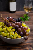 Close up bowl of various grapes: red, white and black berries on the dark wooden table with bottle and glass of white wine in the. Background . Selective focus Stock Photography