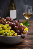 Close up bowl of various grapes: red, white and black berries on the dark wooden table with bottle and glass of white wine in the. Background . Selective focus Royalty Free Stock Images