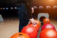 Close up of bowling player hand taking red ball from bowl lift Stock Photography