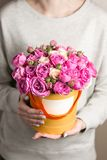 Close up of box with pink spray roses in female hands. copy space. blank for text.  Stock Photography