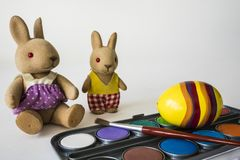 Painting Easter eggs with red brush. Stuffed animals, against white background royalty free stock photos