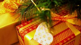 Close-up boxes with gifts lying under branches of artificial Christmas tree. Flashing yellow gerlyanda stock video