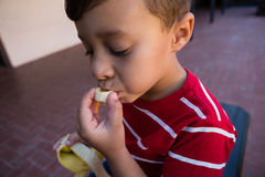 Close up of boy eating banana while sitting on chair Royalty Free Stock Photography