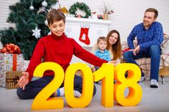 Close-up of a boy with figures 2018, in the background happy family in his house Stock Photography