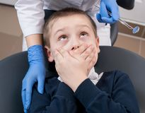 Close-up of boy frightened by dentists covers her mouth and looks for him. Doctor in gloves with one hand holds the instruments with the other hand supports Stock Image