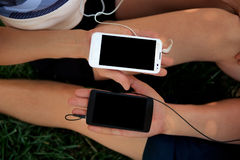 Close-up of boy and girl hands holding two smartphones Royalty Free Stock Photos