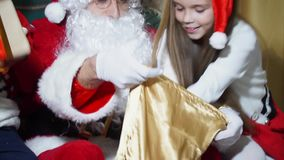 Close-up of a boy and a girl took out the presents from Santa`s bag stock footage