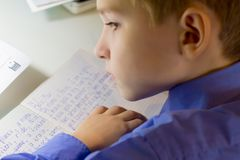 Close-up of boy hand with pencil writing english words by hand on traditional white notepad paper. Boy writes a letter to a friend Royalty Free Stock Photos