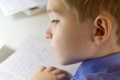 Close-up of boy hand with pencil writing english words by hand on traditional white notepad paper. Boy writes a letter to a friend Stock Photography