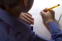 Close-up of boy hand with pencil writing english words by hand on traditional white notepad paper. Boy writes a letter to a friend Stock Image
