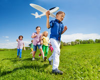 Close-up of boy holding airplane and kids behind Stock Photo