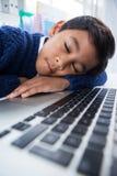 Close up of boy imitating as businessman sleeping on laptop Royalty Free Stock Photos