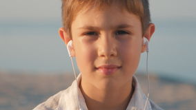 Close-up boy listening to music on headphones. 10-year-old child enjoys a smartphone sitting on the sand on the stock footage