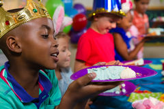 Close up of boy looking at cake in plate Stock Photography
