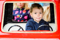 Close Up of a Boy on a Merry-Go-Round Car Stock Images