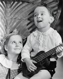 Close-up of a boy playing a guitar with his sister royalty free stock images