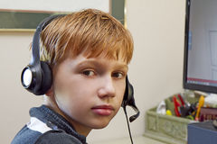 Close-up of Boy Playing Video Games on Computer. Boy wearing headset while playing video games on office computer Stock Photos