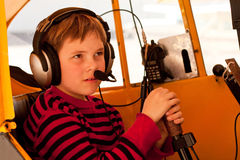 Close up of boy pretending to fly Piper Cub. Close up shot of a cute little nine-year-old boy in the cockpit of a 1946 yellow Piper Cub airplane. He pretends to Stock Photography