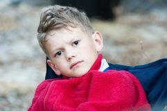 Close-up of a boy in a red fleece on a blue chair stock photography