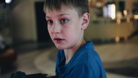 Close-up of the boy`s face in the arcade. In the eyes of reflected outbreaks. Cool footage. Children`s entertainment. Emotions stock video footage