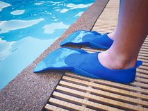 Boy Wearing Blue Swim Fin Flippers by the Swimming Pool stock photo