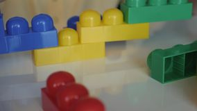 Close-up of the boy`s hand collecting the developing designer lego sitting at the white table. The concept of a happy stock footage