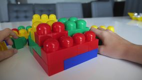 Close-up of the boy`s hand collecting the developing designer lego sitting at the white table. The concept of a happy stock video footage