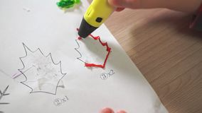 Close-up boy`s hand uses a 3D pen. He creates a plant leaf from red ABS plastic.