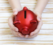 Close up of boy's hands holding piggy bank Royalty Free Stock Images
