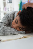 Close up of boy sleeping on book. At desk in office Royalty Free Stock Photo