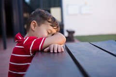 Close up of boy sleeping on table Stock Photography
