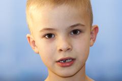 Close-up of boy smiling with missing front milk tooth over light Royalty Free Stock Photos