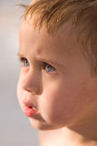 Close-up Boy Squinting Eyes in Sun. Close-up profile photo of a toddler boy face with beautiful hazel green eyes squinting in full sun in the swimming pool. wet stock photography